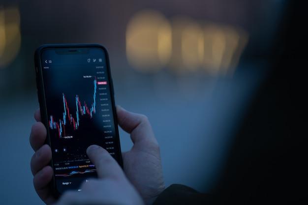 Мужская рука, касающаяся экрана смартфона с графиком форекс в реальном времени, стоя на открытом воздухе, выборочный фокус на мобильном телефоне с финансовым графиком. трейдер проверяет данные фондового рынка в мобильном приложении