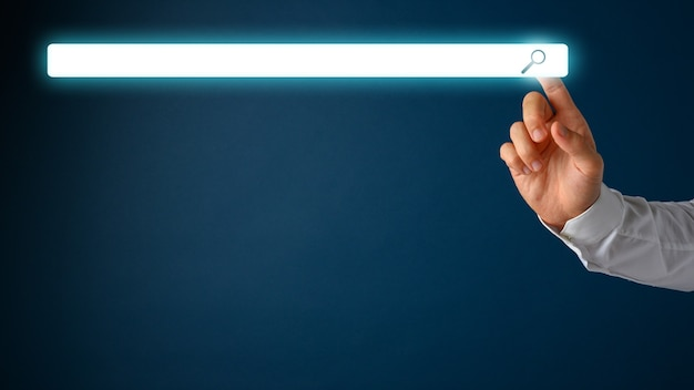 Male hand touching a white glowing empty search bar over navy blue background.