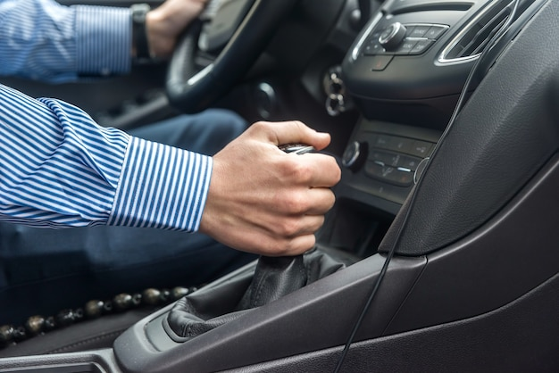 Male hand on transmission lever close up