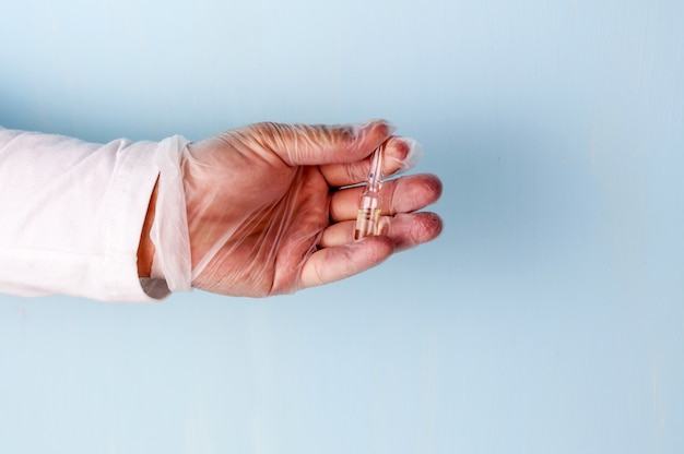 Male hand in a transparent medical nitrile glove holds a vial of medication.