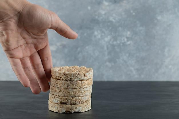 Mano maschio che prova a toccare le torte di riso soffiato sulla superficie di marmo