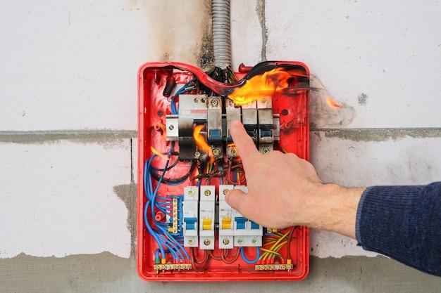 Мужская рука выключает горящий распределительный щит от перегрузки или короткого замыкания на стене
