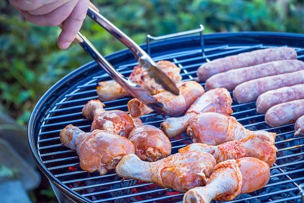 Мужская рука переворачивает сырое мясо щипцами