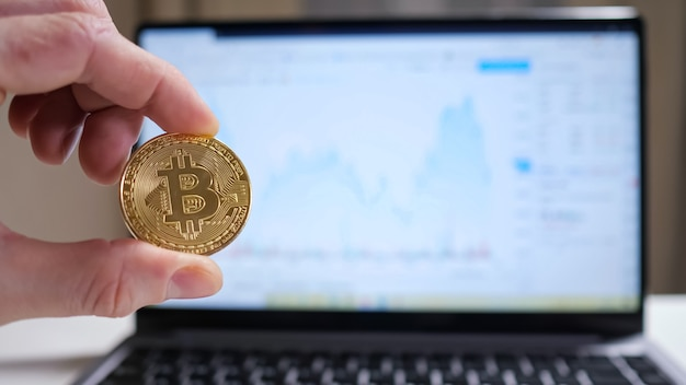 Male hand twirls bitcoin on the background of the laptop, showing the graph.