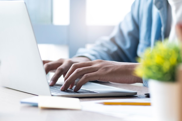 ノートパソコンのキーボードで入力する男性の手。