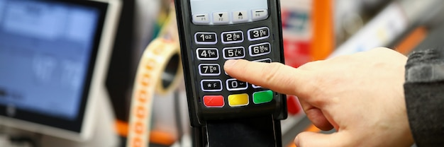 Male hand typing pin code card while paying with it at cash desk of supermarket close-up