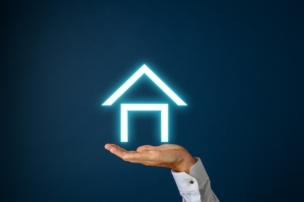 진한 파란색 인터페이스 화면에 흰색 빛나는 집 아래 남성 손.