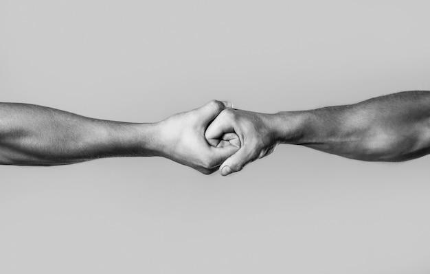 악수에 연합된 남성 손입니다. 남자는 손, 후견인, 보호를 도와줍니다. 두 손, 고립된 팔, 친구의 도움의 손길. 친절한 악수, 친구 인사말. 구조, 도움의 손길. 검정색과 흰색.