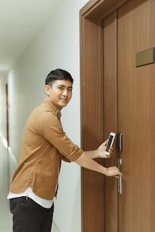 センサースキャンにスマートフォンを使用している男性の手。自動ドアアクセスとセキュリティのための赤外線センサー技術。