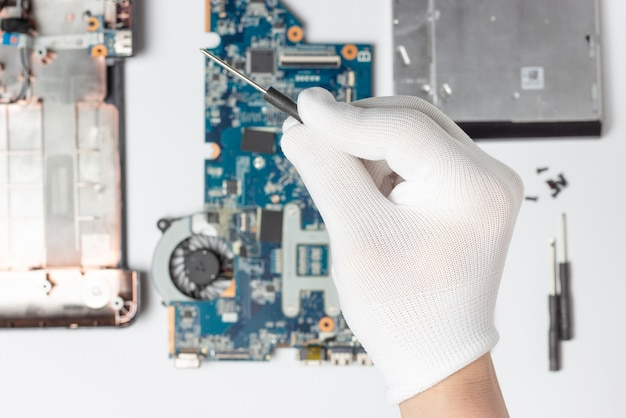 A male hand in a white glove holds a screwdriver in his hands against the background of disassembled laptop top view.