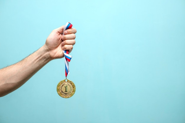 The male hand of the winning athlete holds the gold medal