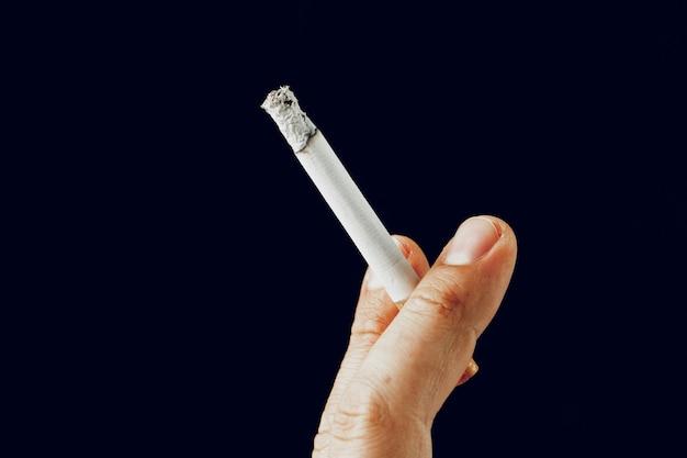 Мужская рука с горящей сигаретой на черном фоне