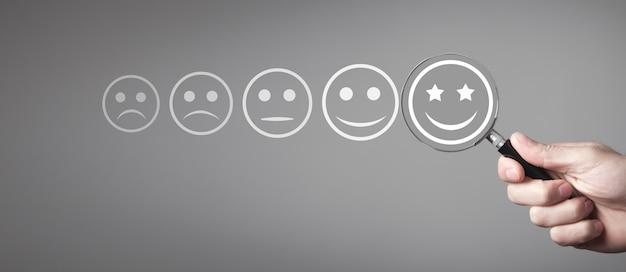 돋보기가있는 남성 손은 훌륭한 웃는 얼굴을 선택합니다. 비즈니스 고객 서비스. 평가. 피드백