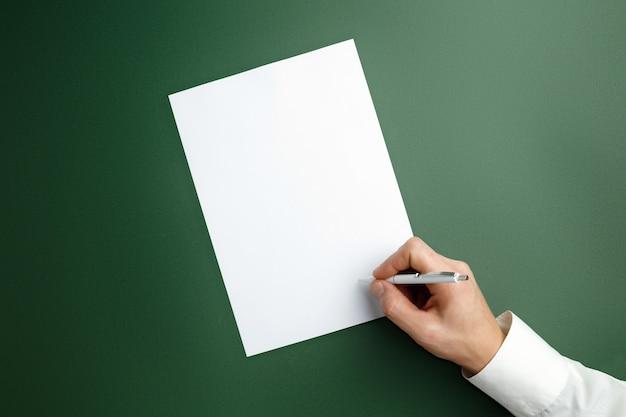 Мужская рука с ручкой и писать на пустой лист на зеленой стене.