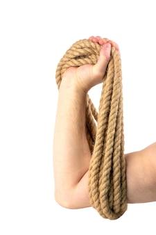 Мужская рука с мотком веревки, изолированной на белой стене