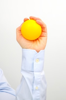 흰색 표면에 노란색 공을 남성 손