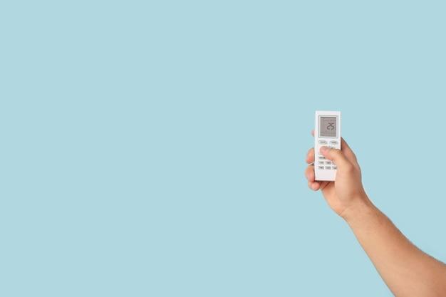 Мужская рука с пультом дистанционного управления кондиционером на цветном фоне