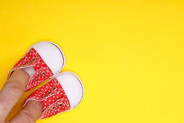 Мужская рука с детской обувью красного цвета с белыми точками в горошек на желтом фоне