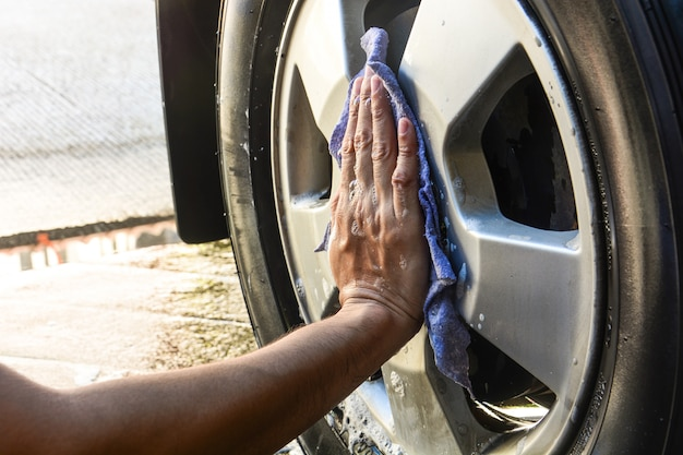 Male hand with blue cloth washing wheel car
