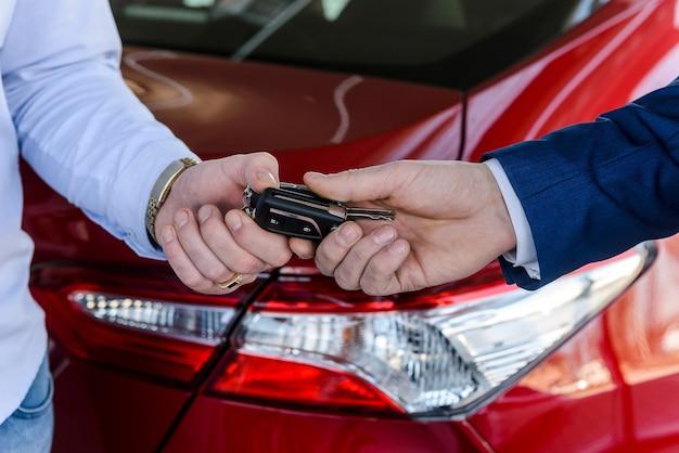 Мужская рука с ключами от машины против новой машины в автосалоне