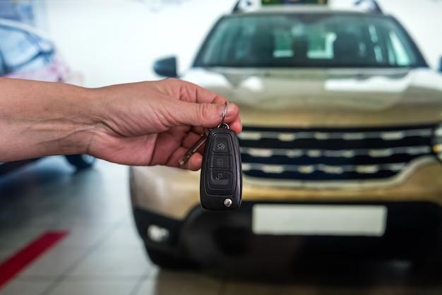Мужская рука с ключами от машины перед автомобилем