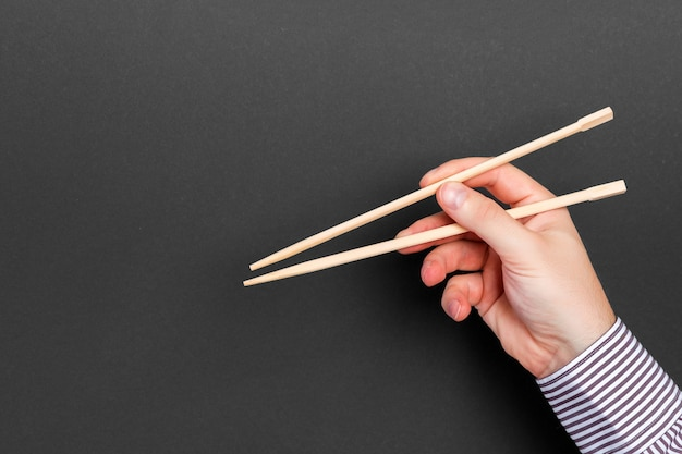 Male hand with chopsticks on black background. traditional asian food with emty space for your design.