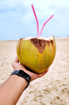 Male hand with a coconut on the beach