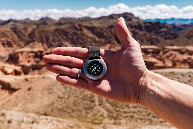 Male hand with compass on background of mountains in summer, point of view.