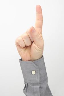 흰색 표면에 대해 제기 집게 손가락으로 남성 손