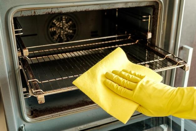 Мужская рука с перчатками чистит духовку