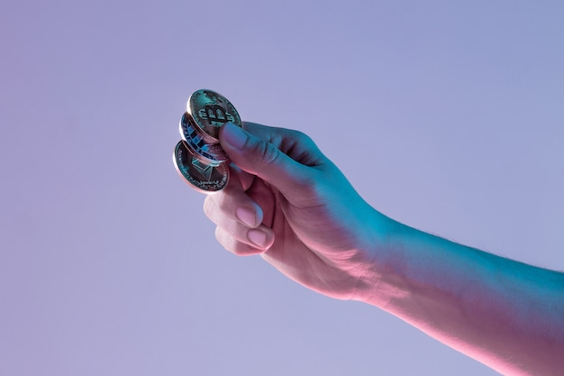 青の背景に黄金のビットコインを持つ男性の手