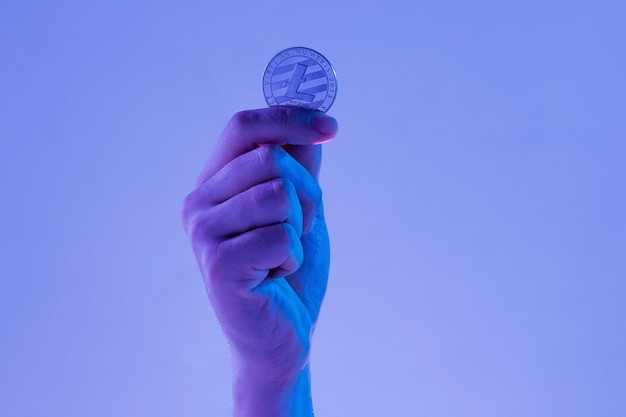 Мужская рука с золотым litecoin на синем фоне