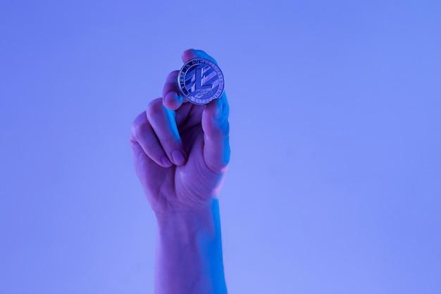 青の背景に黄金のlitecoinを持つ男性の手