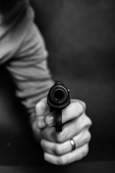 Male hand with gun isolated on black background. man with a gun ready to shoot, focus on the weapon.