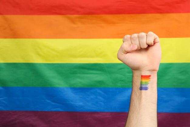Мужская рука с радугой лгбт против флага лгбт