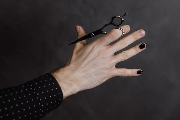 The male hand with manicure holds scissors for a hairstyle on gray