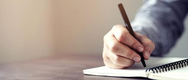 Мужская рука с ручкой, писать на ноутбуке