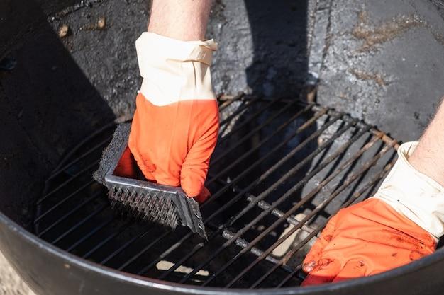 Мужская рука в красных перчатках жесткой щеткой чистит круглый гриль.