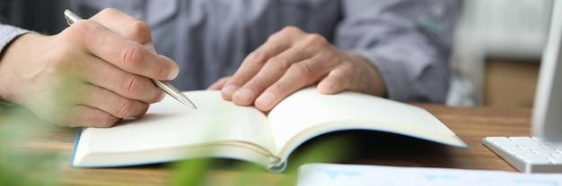 ノートにリングを書く男性の手