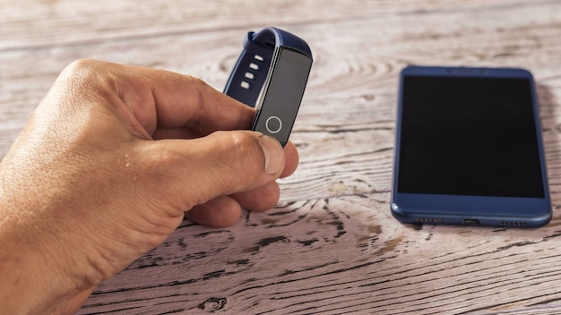スマートブレスレットと木製のテーブルの上のスマートフォンを持つ男性の手。スポーツをコントロールするアクセサリー。スポーツスタイル。