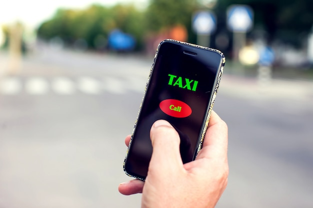 Male hand with smartphone on blurred road. taxi service application on screen.