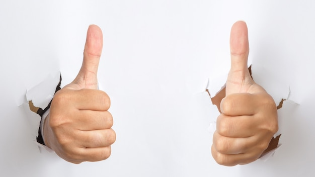 Male hand  with thumb up gesture punching through the paper