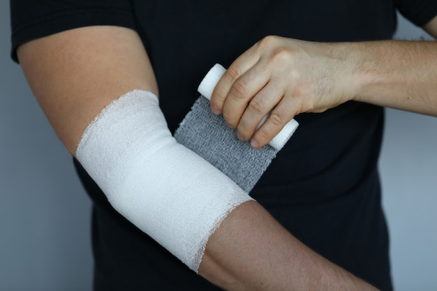 Male hand with tight elastic bandage on elbow closeup