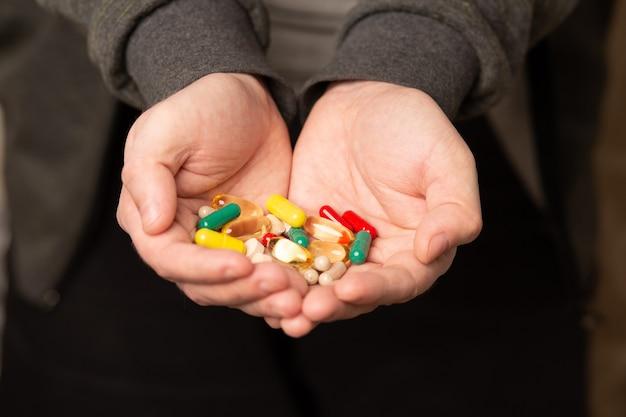 건강한 삶을 위한 다양한 알약과 일일 보충제가 있는 남성 손