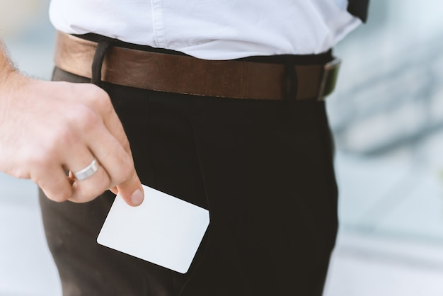 Male hand with white empty business card near pocket, close-up photo with selective focus