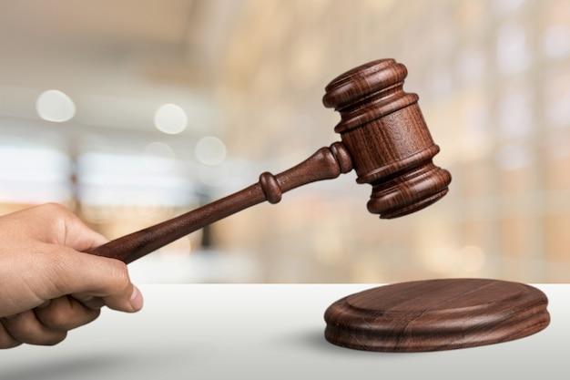 背景に木製の裁判官ハンマーと男性の手