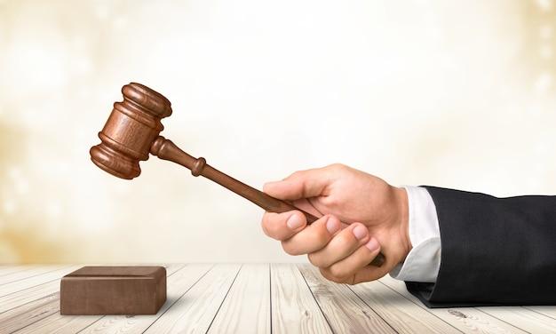明るい背景に木製の裁判官ハンマーと男性の手