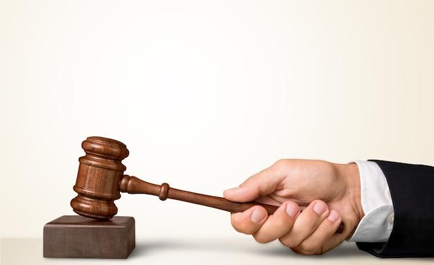 木製の裁判官のハンマー、背景の本と棚の男性の手