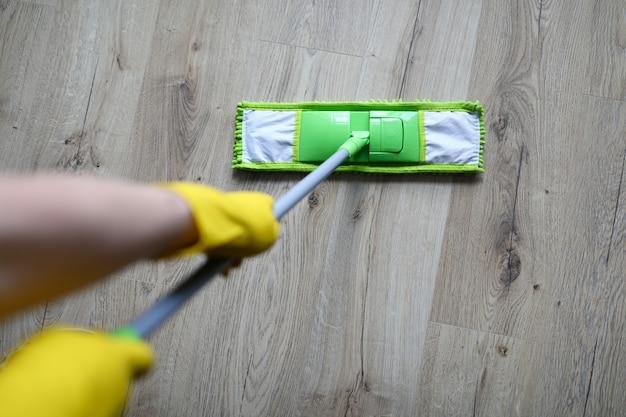 黄色の保護手袋を持つ男性の手は緑のプラスチックモップを保持します