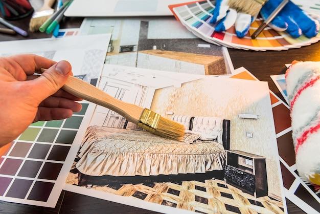 Male hand work with color sampler for design home. apartament sketch at office desk